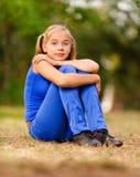 Adolescente que se sienta en verde Foto de archivo libre de regalías