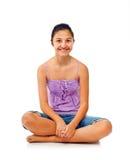 Adolescente que se sienta mientras que disfruta con los brazos para arriba Foto de archivo