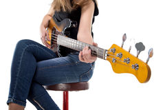 Adolescente que se sienta que juega en la guitarra baja Imagen de archivo