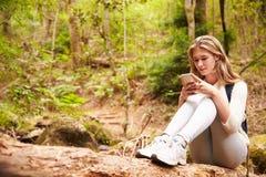 Adolescente que se sienta solamente en un bosque usando un smartphone Foto de archivo