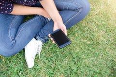 Adolescente que se sienta que sostiene el teléfono elegante en las manos Fotografía de archivo