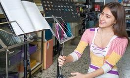Adolescente que selecciona el soporte de música Foto de archivo