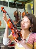 Adolescente que selecciona el violín en tienda Fotografía de archivo libre de regalías