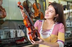 Adolescente que selecciona el violín en tienda Foto de archivo