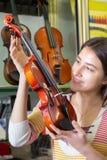 Adolescente que selecciona el violín en tienda Imagen de archivo