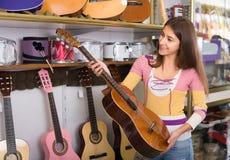 Adolescente que selecciona la guitarra en tienda Imagenes de archivo