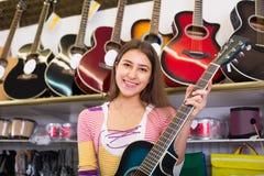 Adolescente que selecciona la guitarra en tienda Fotos de archivo