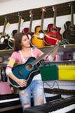 Adolescente que selecciona la guitarra en tienda Fotografía de archivo libre de regalías