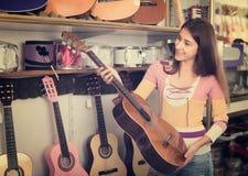 Adolescente que selecciona la guitarra en tienda Imagen de archivo