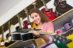 Adolescente que selecciona la guitarra en tienda Foto de archivo