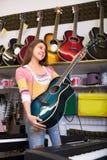Adolescente que selecciona la guitarra en tienda Foto de archivo libre de regalías