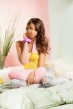 Adolescente que senta-se em sua cama foto de stock royalty free