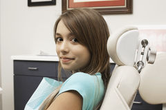 Adolescente (14-16) que senta-se na cadeira do dentista na cirurgia dental, sorrindo, vista lateral, retrato Foto de Stock