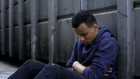 Adolescente que senta-se na entrada, emigrante da virada que enfrenta dificuldades da vida, sem abrigo imagens de stock