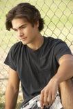 Adolescente que senta-se no campo de jogos Foto de Stock Royalty Free