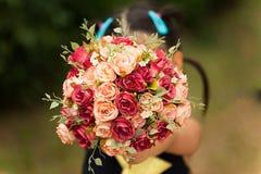 Adolescente que sente a terra arrendada feliz um ramalhete das flores na estação do amor imagem de stock royalty free