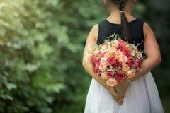 Adolescente que sente a terra arrendada feliz um ramalhete das flores na estação do amor foto de stock royalty free