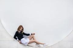 Adolescente que sienta en la calle el fondo blanco Fotografía de archivo
