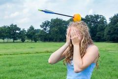 Adolescente que siente temeroso con la manzana y la flecha en la cabeza Fotografía de archivo libre de regalías