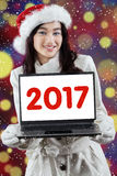 Adolescente que sonríe con 2017 en el ordenador portátil Fotografía de archivo libre de regalías