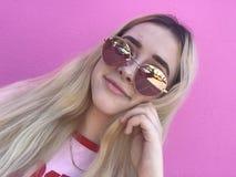 Adolescente que sonríe con las gafas de sol y el pelo largo Foto de archivo libre de regalías