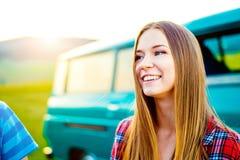 Adolescente que sonríe contra exterior campervan verde en naturaleza Imagen de archivo