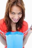 Adolescente que sonríe después de mirar su bolso de la compra Imágenes de archivo libres de regalías
