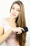 Adolescente que sonríe mientras que cepilla el pelo largo en estudio Fotografía de archivo