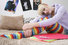 Adolescente que sonríe mientras que se sienta en cama Fotos de archivo