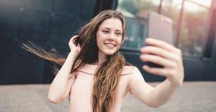 Adolescente que sonríe mientras que toma un selfie Imagen de archivo