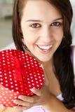 Adolescente que sonríe y que sostiene el rectángulo de regalo rojo Imagen de archivo