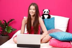 Adolescente que sonríe y que usa la computadora portátil Foto de archivo