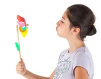 Adolescente que sopla un molinillo de viento coloreado Foto de archivo