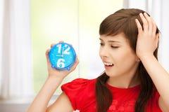 Adolescente que sostiene el despertador Foto de archivo libre de regalías