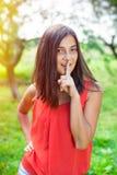 Adolescente que sostiene el finger cerca de los labios Fotografía de archivo