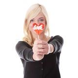 Adolescente que sostiene el lollipop en forma de corazón rojo Imagenes de archivo