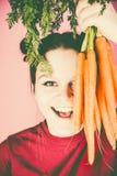 Adolescente que sostiene el manojo de zanahorias frescas sobre fondo rosado Imágenes de archivo libres de regalías