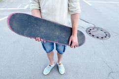 Adolescente que sostiene el monopatín mientras que se coloca en el centro de la calle Imagen de archivo libre de regalías
