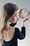 Adolescente que sostiene el pequeño espejo roto Imagen de archivo