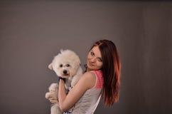Adolescente que sostiene el perrito maltés Fotografía de archivo libre de regalías