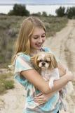 Adolescente que sostiene el perro que camina en un camino de tierra Imagen de archivo libre de regalías