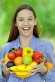 Adolescente que sostiene el plátano, las pimientas, las peras y las naranjas Foto de archivo libre de regalías
