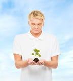 Adolescente que sostiene el suelo con una planta Imagenes de archivo