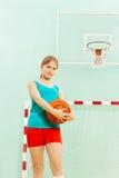 Adolescente que sostiene la bola durante partido de baloncesto Foto de archivo libre de regalías