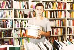 Adolescente que sostiene la pila de libros Fotografía de archivo libre de regalías