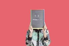Adolescente que sostiene la pizarra con smiley en blanco de la expresión en él sobre fondo rojo Fotografía de archivo libre de regalías