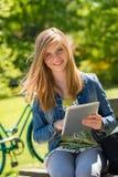 Adolescente que sostiene la tableta digital en parque Imagenes de archivo