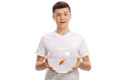 Adolescente que sostiene un cuenco con un pez de colores dentro Imagen de archivo
