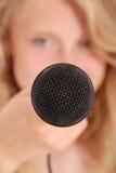 Adolescente que sostiene un micrófono en frente Foto de archivo