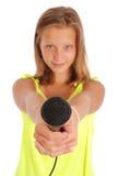 Adolescente que sostiene un micrófono en frente Fotos de archivo